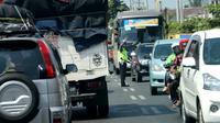 Seorang polisi mengatur lalu lintas di ruas Jalan Lintas Selatan (JLS) Kebumen. (Liputan6.com/Muhamad Ridlo)