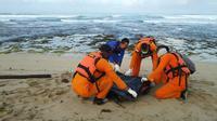 Petugas Basarnas tengah mengevekuasi salah satu korban tenggelam di pantai Cijeruk, Cibalong Garut  (Liputan6.com/Jayadi Supriadin)