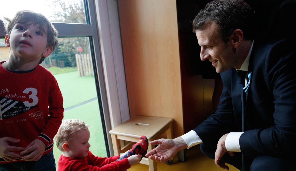 Presiden Prancis Emmanuel Macron bermain dengan anak-anak saat mengunjungi Graffiti's- Association Le Moulin Vert di Normandia, Prancis (5/4). Pada kunjungannya Presiden Emmanuel Macron berinteraksi dengan anak-anak autis. (AP / Christophe Ena, Pool)