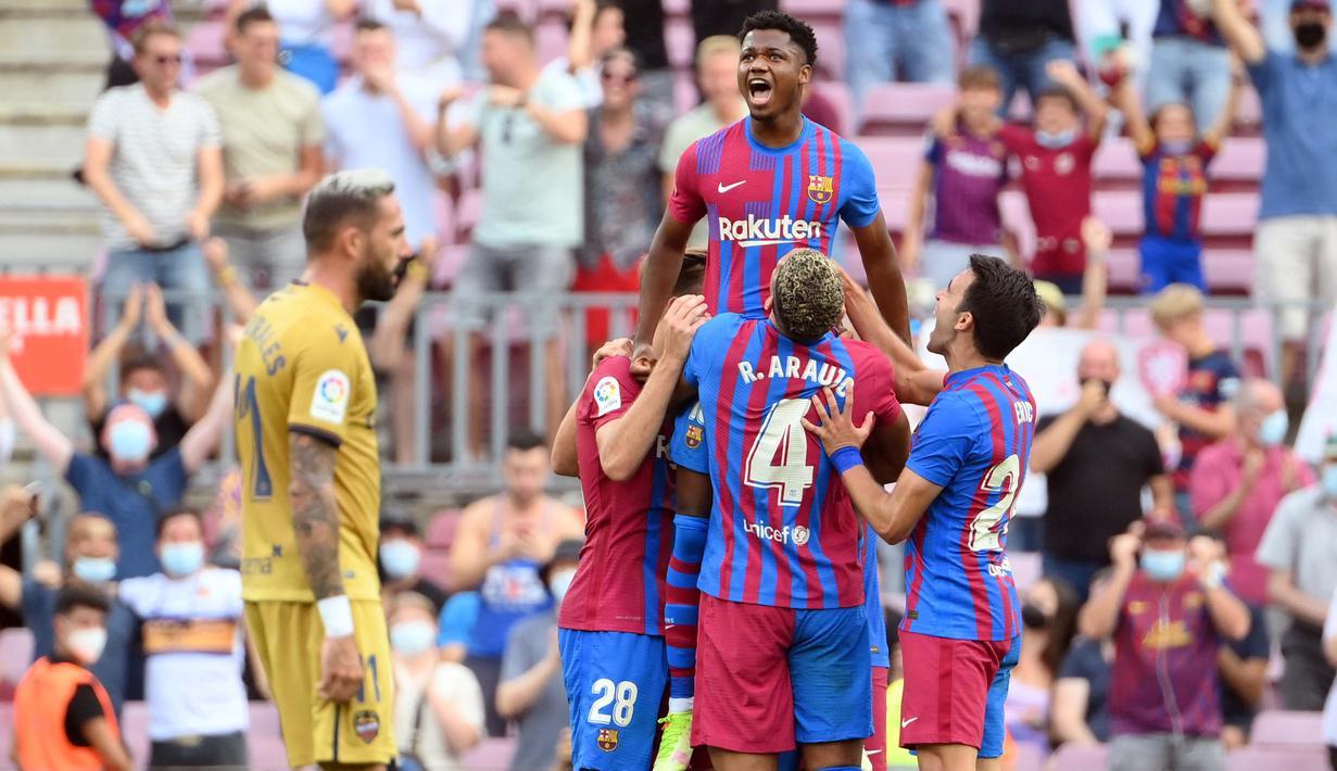 Ansu Fati yang tampil untuk pertama kali bagi Barcelona langsung menorehkan namanya di papan skor saat timnya mengalahkan Levante 3-0. Sontak seluruh pemain langsung menghampiri dan mengangkatnya layaknya seorang raja. (AFP/Lluis Gene)