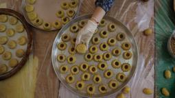 Perempuan Palestina dengan masker dan sarung tangan menyiapkan biskuit tradisional menjelang Idul Fitri di sebuah rumah di kota tua Hebron, Tepi Barat yang diduduki, Selasa (19/5/2020). Biskuit-biskuit itu akan dijual secara online guna menjaga jarak selama pandemi Covid-19. (HAZEM BADER/AFP)