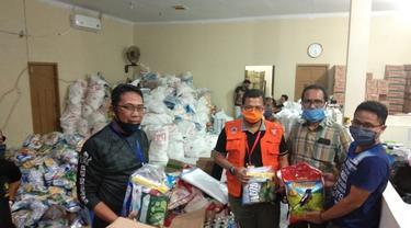 Kepala Dinas Sosial Kota Makassar sedang memperlihatkan paket sembako Covid-19 (Liputan6.com/ Eka Hakim)