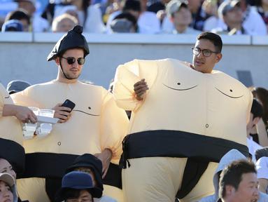 Tiga orang pria mengenakan kostum sumo bersiap menyaksikan pertandingan Rugby World Cup Pool C antara Argentina dan Amerika Serikat di Kota Kumagaya, Jepang (9/10/2019).  Rugby World Cup diselenggarakan dari 20 September hingga 2 November 2019. (AP Photo/Eugene Hoshiko)