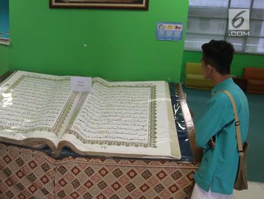 Pengunjung mengamati Alquran raksasa yang dipajang di perpustakaan Jakarta Islamic Centre, Jakarta Utara, Jumat (18/5). Alquran yang ditulis tangan tersebut sudah berusia 16 tahun. (Liputan6.com/Arya Manggala)