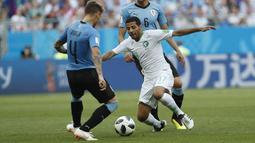Pemain Arab Saudi, Taiseer Aljassam (tengah) berusaha melewati adangan pemain Uruguay, Guillermo Varela pada laga grup A Piala Dunia 2018 di Rostov Arena, Rostov-on-Don, Rusia, (20/6/2018). Uruguay menang 1-0. (AP/Darko Vojinovic)