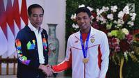 Presiden Joko Widodo atau Jokowi (kiri) bersalaman dengan sprinter Lalu Muhammad Zohri (kanan) di Istana Bogor, Jawa Barat, Rabu (18/7). Zohri tampak mengenakan medali emas yang diraihnya di Finlandia. (Liputan6.com/Pool/Biro Pers Setpres)