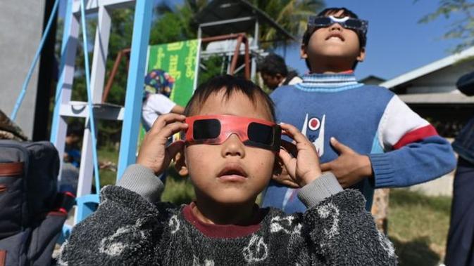 Anak-anak di Wan Twin, Myanmmar menggunakan kacamata khusus untuk menyaksikan gerhana matahari cincin.  (Source: AFP)