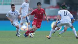 Pemain Korea Utara, Jon Se Gye berusaha melewati adangan pemain Uzbekistan pada laga PSSI Anniversary Cu 2018 di Stadion Pakansari, Bogor, (26/4/2018). Uzbekistan bermain imbang 2-2. (Bola.com/Nick Hanoatubun)