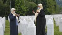 Dua wanita berdoa di pemakaman korban pembantaian Sreberenica, Potocari, Bosnia, 7 Juli 2020. Lebih dari 8.000 muslim Bosnia tewas dalam 10 hari pembantaian setelah kota itu dikuasai pasukan Serbia pada bulan-bulan terakhir perang saudara 1992-1995. (AP Photo/Kemal Softic)