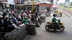 Pengendara motor melintas di perlintasan kereta api di kawasan Roxy, Jakarta, Rabu (21/3). Petugas Sudinhub Jakpus telah menutup akses perlintasan KA di depan Roxy 20 September 2017, namun mendapat protes keras dari warga.  (Liputan6.com/Arya Manggala)