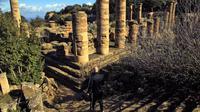 Seorang pria menuruni tangga di situs kota Yunani kuno Kirene di pinggiran kota Shehhat, Libya (13/12/2019). Kota tua Yunani ini menjadi bagian dari imperium yang dikuasai oleh Dinasti Ptolemeus dari Alexandria di Mesir dan jatuh ke tangan Kekaisaran Romawi.  (AFP/Abdullah Doma)