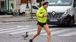 Seorang warga sedang berjoging melewati seekor bebek di Paris, Prancis (6/4/2020). Selama lockdown, orang-orang diharuskan tetap berada di rumah, kecuali untuk urusan pekerjaan, keperluan kesehatan, atau belanja kebutuhan. (Xinhua/Aurelien Morissard)