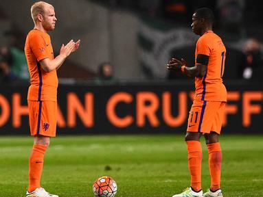 Gelandang Belanda, Davy Klaassen bersama Quincy Promes memberikan penghormatan untuk Johan Cruyff pada laga persahabatan melawan Prancis di Stadion Amsterdam Arena, Amsterdam, Jumat (25/3/2016). Belanda takluk 2-3 dari Prancis. (AFP/Franck Fife)