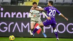 Pemain AS Roma, Borja Mayoral, berusaha melewati pemain Fiorentina, German Pezzella, pada laga Liga Italia di Stadion Artemio Franchi, Rabu (3/3/2021). AS Roma menang dengan skor 2-1. (Jennifer Lorenzini/LaPresse via AP)