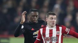 Bek Manchester United, Aaron Wan-Bissaka berusaha merebut bola yang dibawa gelandang Sheffield United, John Fleck pada pertandingan lanjutan Liga Inggris di Stadion Bramall Lane (24/11/2019). MU bermain imbang 3-3 atas Sheffield Unite. (AP Photo/Jon Super)