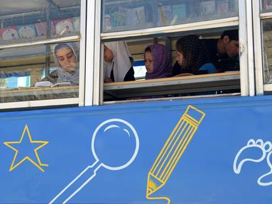 Anak-anak Afghanistan membaca buku dalam bus yang dijadikan perpustakaan keliling di Kabul, 4 April 2018. Charmaghz, nama bus keliling tersebut yang dalam bahasa setempat berarti 'kacang kenari', karena bentuknya menyerupai otak manusia. (AFP/Shah MARAI)