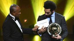 Winger Liverpool, Mohamed Salah menerima penghargaan Pemain Terbaik Afrika 2018 dalam malam penghargaan di Dakar, Senegal, Selasa (8/1). Mohamed Salah mengungguli rekan setimnya, Sadio Mane dan bomber Arsenal, Pierre-Emerick Aubameyang. (SEYLLOU/AFP)
