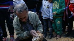 Pemilik kebun binatang Fathi Jumaa saat menguburkan mayat empat anak singa di kebun binatangnya di kamp pengungsi Rafah, Gaza (18/1). Fathi mengatakan ia menutupi sangkar singa-singa dengan selimut jelang badai musim dingin. (AP Photo/Adel Hana)