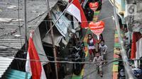 Anak-anak melintas di Gang A, RT 10/11, Pademangan Timur, Jakarta, Rabu (5/8/2020). Ide menghias gang tersebut dicetus oleh Ketua RT setempat, Farli (48), dan disambut antusias oleh warga yang turut membantu pemasangan atribut HUT ke-75 RI secara swadaya. (merdeka.com/Iqbal S. Nugroho)