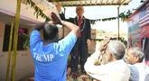 Petani Bussa Krishna (kiri) bersama rekan-rekannya melakukan penyembahan di depan patung Presiden AS Donald Trump saat memanjatkan doa  di Desa Konney, Telangana, negara bagian India selatan (14/2/2020). Bussa Krishna merupakan penggemar berat Presiden AS, Donald Trump. (AFP/Noah Seelam)