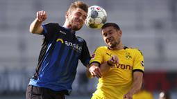 Pemain Borussia Dortmund, Raphael Guerreiro, berebut bola dengan pemain SC Paderborn 07, Dennis Srbeny, pada laga Bundesliga di Stadion Benteler, Minggu (31/5/2020). Borussia Dortmund menang dengan skor 6-1 SC Paderborn 07. (AP/Lars Baron)