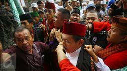 Massa mengamankan seorang pria yang diduga provokator saat sidang kasus penistaan agama di Jakarta, Selasa (10/1). Sempat terjadi kericuhan akibat peristiwa tersebut. (Liputan6.com/Immanuel Antonius)