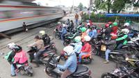Kereta melintas di perlintasan kereta api yang tidak berpalang pintu di kawasan Roxy, Jakarta, Rabu (21/3). Pembukaan celah untuk akses sepeda motor di pintu perlintasan kereta api tersebut sangat membahayakan. (Liputan6.com/Arya Manggala)