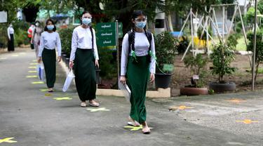 Para siswa yang mengenakan pelindung wajah dan masker berjalan dengan menjaga jarak sosial pada hari pendaftaran sekolah di Yangon, Myanmar (13/7/2020). Myanmar sejak Selasa (7/7) memulai pendaftaran sekolah untuk tahun ajaran 2020-2021, yang tertunda akibat pandemi COVID-19. (Xinhua/U Aung)