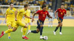 Penyerang Spanyol, Adama Traore, berusaha melewati pemain Ukraina, Ruslan Malinovskiy, pada laga UEFA Nations League di Stadion Olimpiyskiy, Rabu (14/10/2020). Ukraina menang dengan skor 1-0. (AP/Efrem Lukatsky)