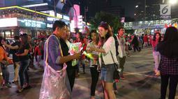 Warga membeli lampu hias kepala pada malam pergantian tahun di MH Thamrin, Jakarta, Minggu (31/12). Pemprov DKI Jakarta memberlakukan car free night mulai pukul 19.00–24.00 WIB.  (Liputan6.com/Angga Yuniar)