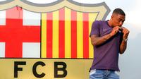 Pesepakbola muda Brasil, Malcom Filipe Silva de Oliveira mencium jersey berlogo Barcelona setibanya di stadion Camp Nou, Selasa (24/7). Barcelona telah membajak Malcolm yang selangkah lagi berkostum AS Roma. (AP Photo/Manu Fernandez)
