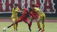 Gelandang Timnas Indonesia U-22, Rafi Syaharil, berebut bola dengan gelandang Bhayangkara FC, Adam Alis, pada laga uji coba di Stadion Patriot, Bekasi, Rabu (6/2). Keduanya bermain imbang 2-2. (Bola.com/Yoppy Renato)