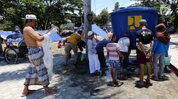 Para pengungsi mengambil wudhu jelang salat Jumat pascagempa dan tsunami di Lapangan Masjid Agung Daru Salam, Palu, Jumat (5/10). Salat digelar di lapangan karena pondasi masjid yang hancur. (Liputan6.com/Fery Pradolo)