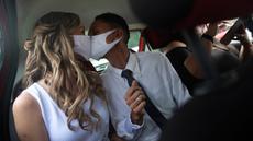 Thiago do Nascimento dan Keilla de Almeida berciuman saat pernikahan drive-thru mereka di kantor pencatatan sipil di Santa Cruz, Rio de Janeiro, Brasil, 28 Mei 2020. Fasilitas ini untuk memudahkan dan membantu pasangan yang ingin mengesahkan hubungan saat pandemi covid-19. (AP/Silvia Izquierdo)