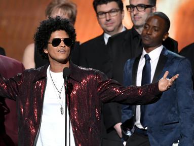 Penyanyi R&B, Bruno Mars mengangkat trofi Album of the Year pada ajang Grammy Awards 2018 di New York City, Minggu (28/1). Tak kurang dari 6 piala Grammy berhasil dibawa pulang termasuk  album of the year untuk 24K Magic. (Kevin Winter/Getty Images/AFP)