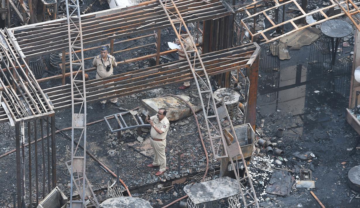 Polisi India menyelidiki sisa-sisa bangunan yang hangus terbakar di sebuah restoran di Mumbai, India (29/12). Restoran yang populer di India tersebut ludes terbakar dan mengakibatkan 15 orang tewas. (29/12 (AFP Photo/Indranil Mukhrejee)