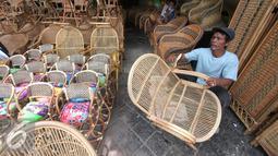 Pekerja rengah saat menguas kursi duduk rotan di Jakarta, Kamis (3/12). Perkumpulan Untuk Peningkatan Usaha Kecil (Pupuk) mendesak pemerintah segera memberlakukan sistem resi gudang rotan. (Liputan6.com/Angga Yuniar)