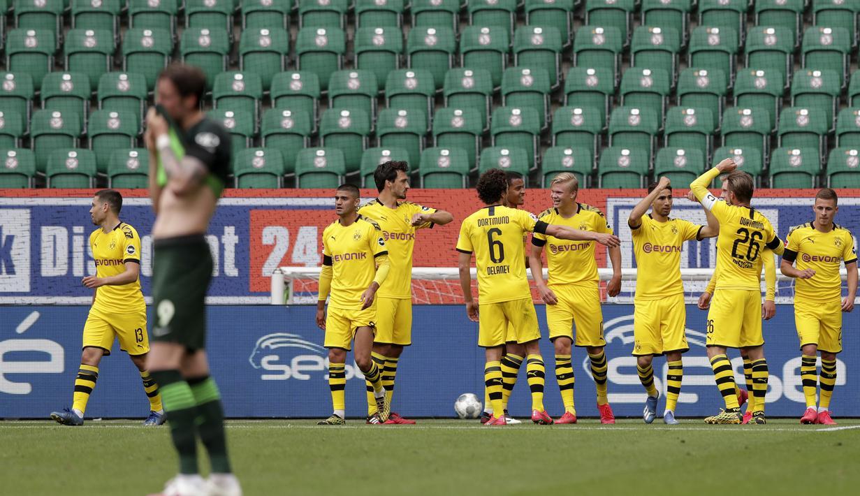 Pemain Borussia Dortmund merayakan gol yang dicetak oleh Raphael Guerreiro ke gawang Wolfsburg pada laga Bundesliga, Minggu (24/5/2020). Borussia Dortmund menang 2-0 atas Wolfsburg. (AP/Michael Sohn)