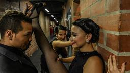 Penari melakukan pemanasan di belakang panggun sebelum tampil dalam Turnamen Menari Tango di Festival Tango Internasional XIII di Medellin, Kolombia (18/6/2019). Festival Tango ini berlangsung dari 16 sampai 24 Juni 2019. (AFP Photo/Joaquin Sarmiento)