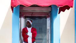 Seorang pria mengenakan pakaian Santa Claus menunggu pelanggan di pintu masuk sebuah kafe di Havana, Kuba (28/12). Havana merupakan kota terbesar dan pelabuhan utama di Kepulauan Hindia Barat. (AP Photo / Desmond Boylan)