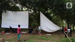 Teknisi menyiapkan layar tancap sebelum pertunjukkan di kawasan Sawangan, Depok, Jawa Barat, Sabtu (11/7/2020). Layar tancap atau bioskop terbuka menjadi alternatif bagi warga untuk menikmati film di tengah penerapan new normal di kawasan Jabodetabek. (Liputan6.com/Herman Zakharia)