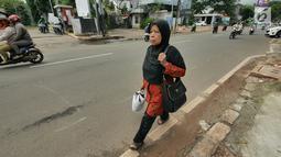 Pejalan kaki berjalan di trotoar kawasan Kemang, Jakarta, Kamis (21/2). Trotoar di Kemang, Jakarta Selatan akan dibangun lebih lebar sehingga ramah pejalan kaki.  (Liputan6.com/Herman Zakharia)