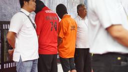 Tersangka dihadirkan saat rilis kasus penyelundupan perangkat telekomunikasi elektronik di Polda Metro Jaya, Jakarta, Kamis (29/8/2019). Polda Metro Jaya menangkap empat orang pelaku penyelundupan 5.572 HP berbagai merek dari China ke Jakarta. (Liputan6.com/Immanuel Antonius)
