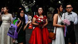 Pasangan pengantin keturunan Tionghoa antre untu mendaftarkan pada acara pernikahan massal di Kuil Thean Hou, Kuala Lumpur, Senin (9/9/2019). Upacara pernikahan massal diadakan untuk 99 pasangan pada hari kesembilan bulan kesembilan yang dianggap sebagai tanggal keberuntungan. (Mohd RASFAN / AFP)