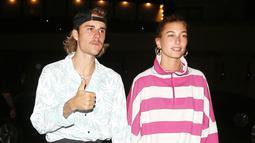 Nah kalau ini Justin Bieber mulai bergaya 80-an. Sementara Hailey menggunakan oversized sweatshirt berwarna pink garis-garis putih. (Mega/USWeekly)