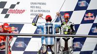 Saat menaiki podium juara, Valentino Rossi memakai jersey timnas Argentina dengan nama Diego Maradona yang merupakan legenda tim Tango. (AP Photo/Natacha Pisarenko)