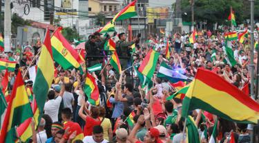 Orang-orang mengibarkan bendera Bolivia merayakan pengunduran diri Presiden Evo Morales di La Paz, Minggu (10/11/2019). Morales memutuskan mengundurkan diri buntut aksi protes yang dilatarbelakangi dugaan dirinya melakukan kecurangan dalam pemilu dalam beberapa pekan terakhir. (JORGE BERNAL/AFP)