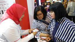 Karyawan Bank DKI menjelaskan aplikasi JakOne Mobile kepada pengunjung Pekan Raya Jakarta di Jakarta (23/5). Bank DKI turut berpartisipasi dalam PRJ sebagai alat pembayaran dengan menggunakan fitur scan to pay. (Liputan6.com/Pool/Budi)