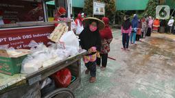 """Warga terdampak Covid-19 antre mendapatkan paket makanan di Cipulir, Jakarta Jumat (18/12/2020). Bantuan langsung kepada 8.000 kepala keluarga disalurkan melalui Foodbank of Indonesia (FOI) sebagai kelanjutan dari kampanye """"DBS Stronger Together Fund"""". (Liputan6.com/Fery Pradolo)"""