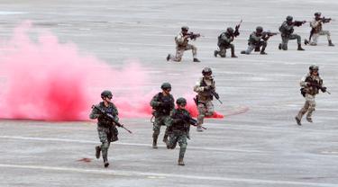 Tentara pasukan khusus Taiwan berlari melewati asap selama latihan tahunan Han Kuang di sebuah pangkalan udara di Taichung, Kamis (7/6). Latihan militer tahunan terbesar ini digelar di tengah kian agresifnya China terhadap Taiwan. (AP/Chiang Ying-ying)